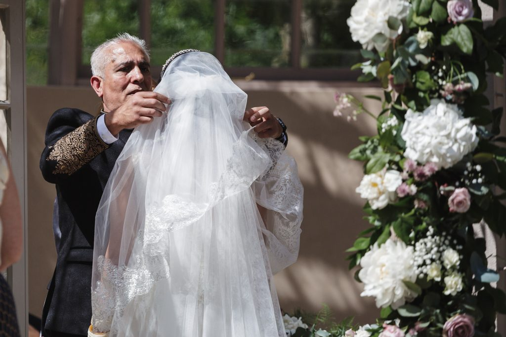 bride's father lifting her veil