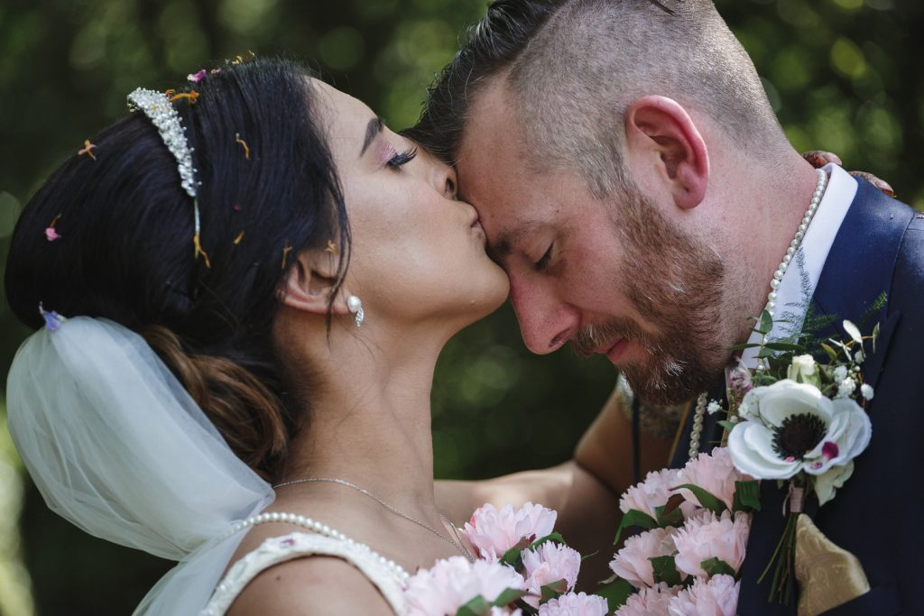 bride kisses the grooms forehead