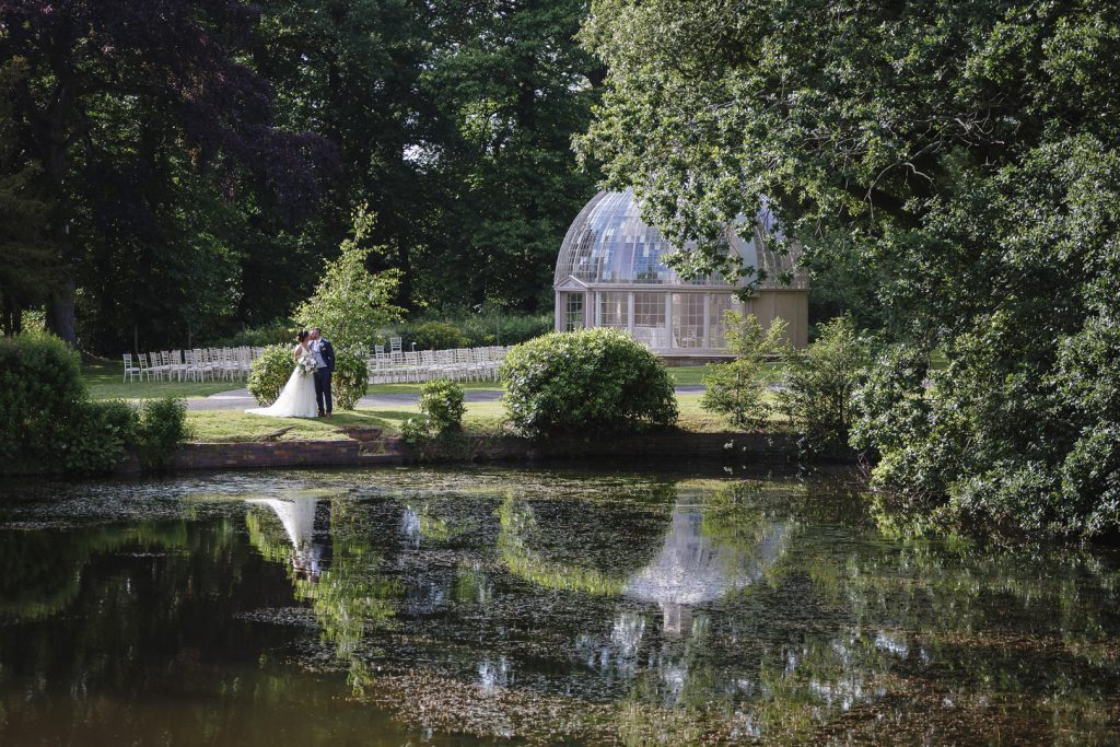 bride and groom portrait across the lake after their Hilton Hall wedding in Wolverhampton