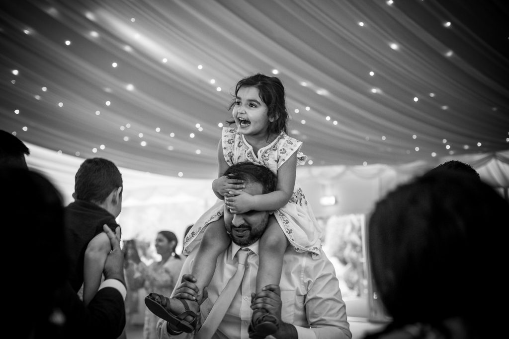 little girl dancing on her fathers shoulders