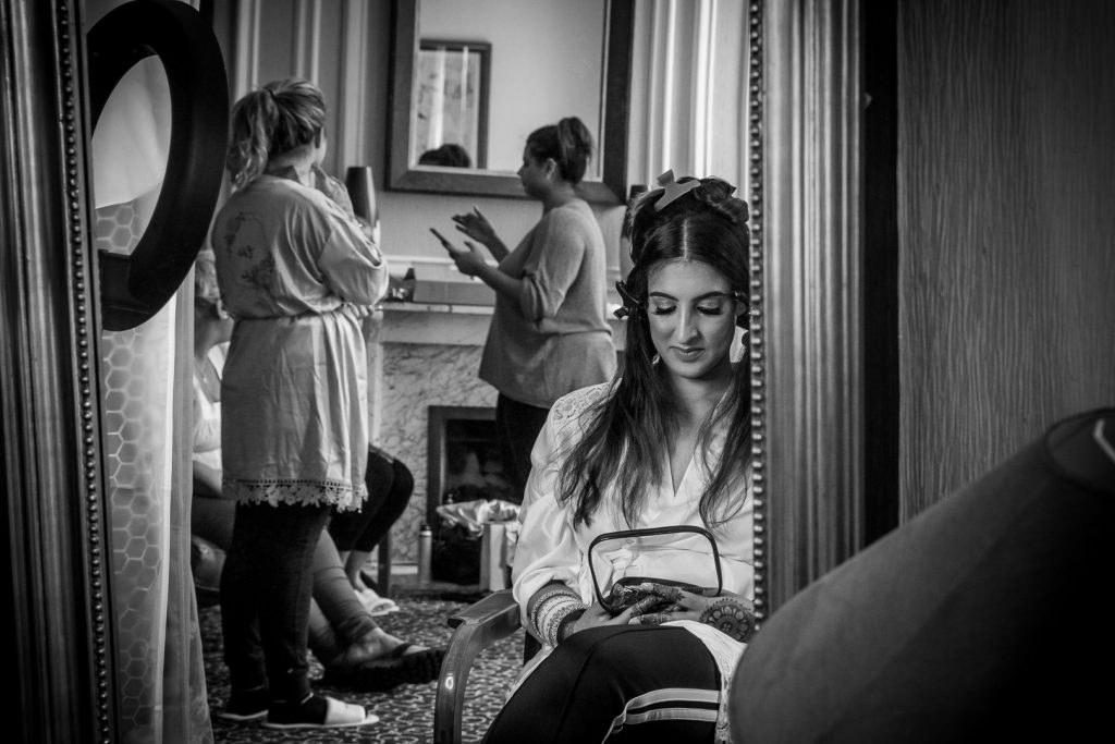 Mirror reflection of bride contemplating whilst getting ready for her Hilton Hall wedding