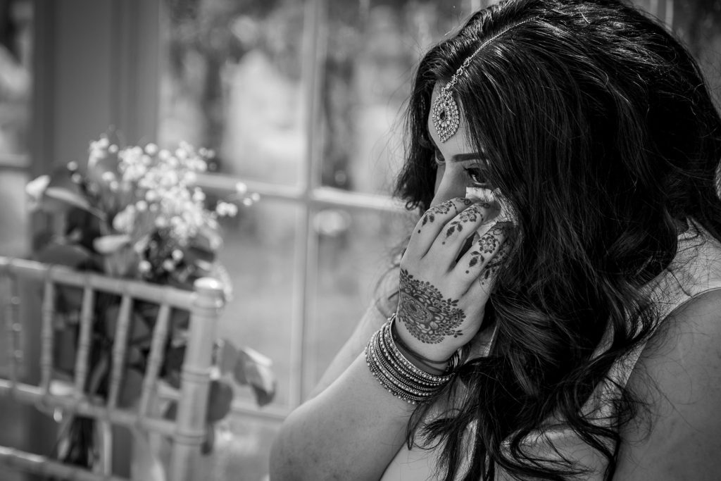 bride's sister wipes away a tear
