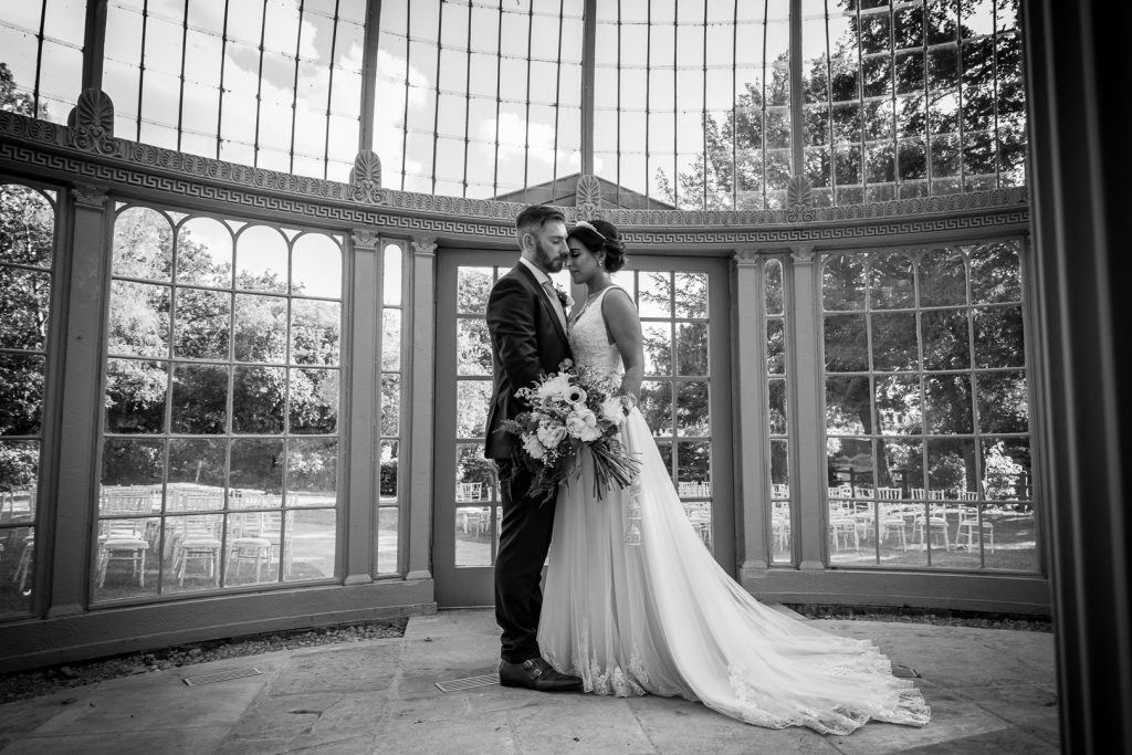 bride and groom portrait in the glass dome at their Hilton Hall wedding