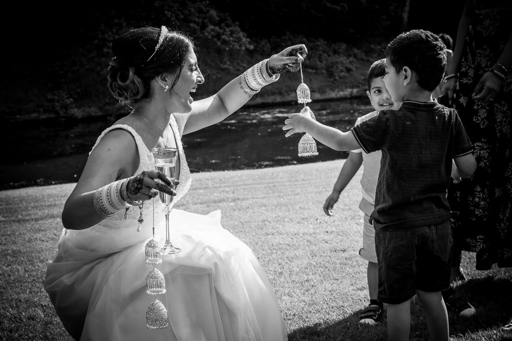 Bride playing with the children at her Hilton Hall wedding