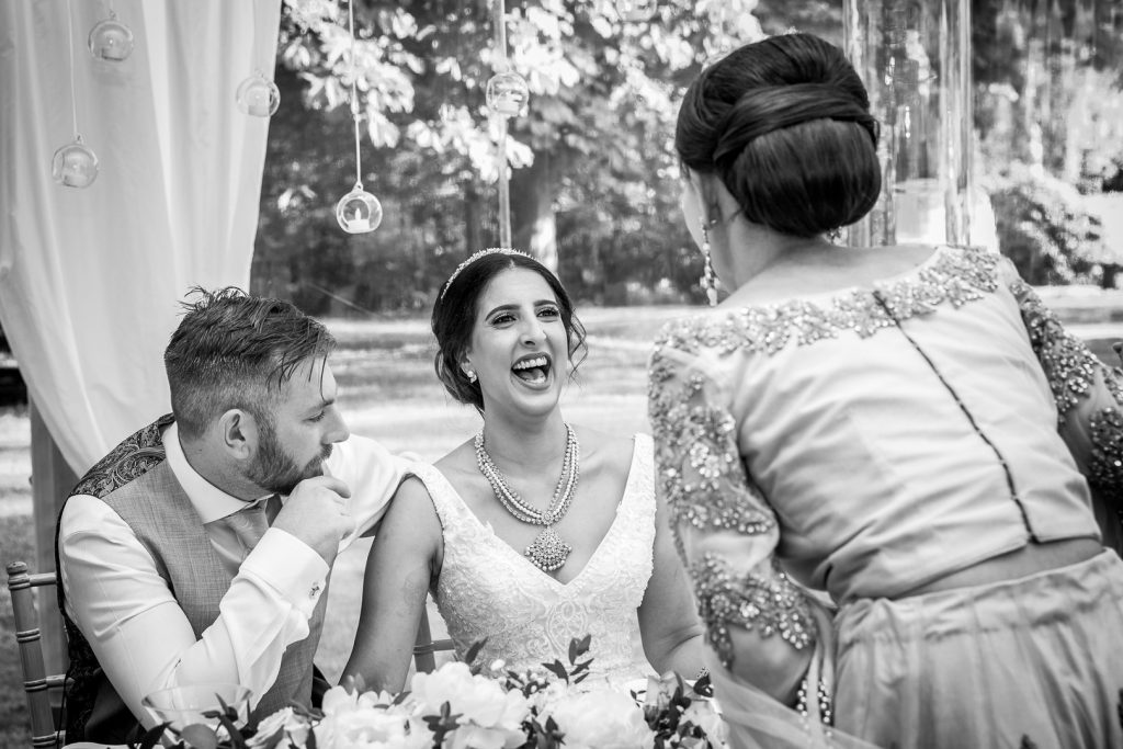 Bride laughing with a guest at her Hilton Hall Wedding