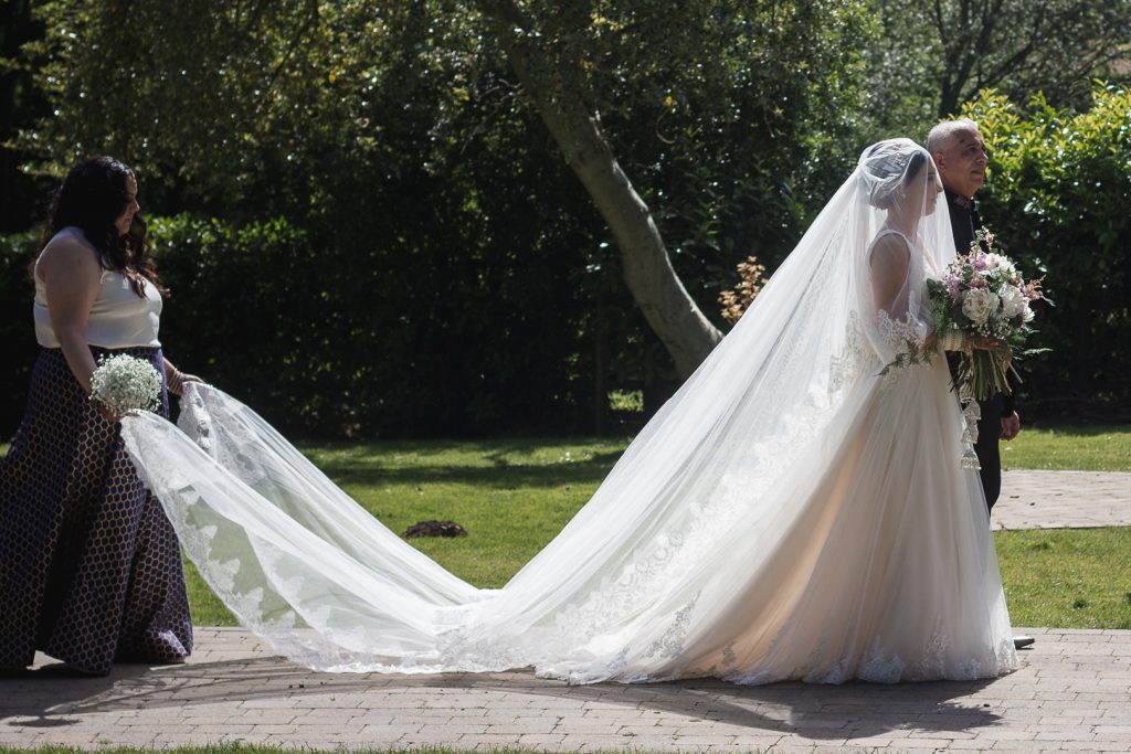 Bride walking with her long veil behind her