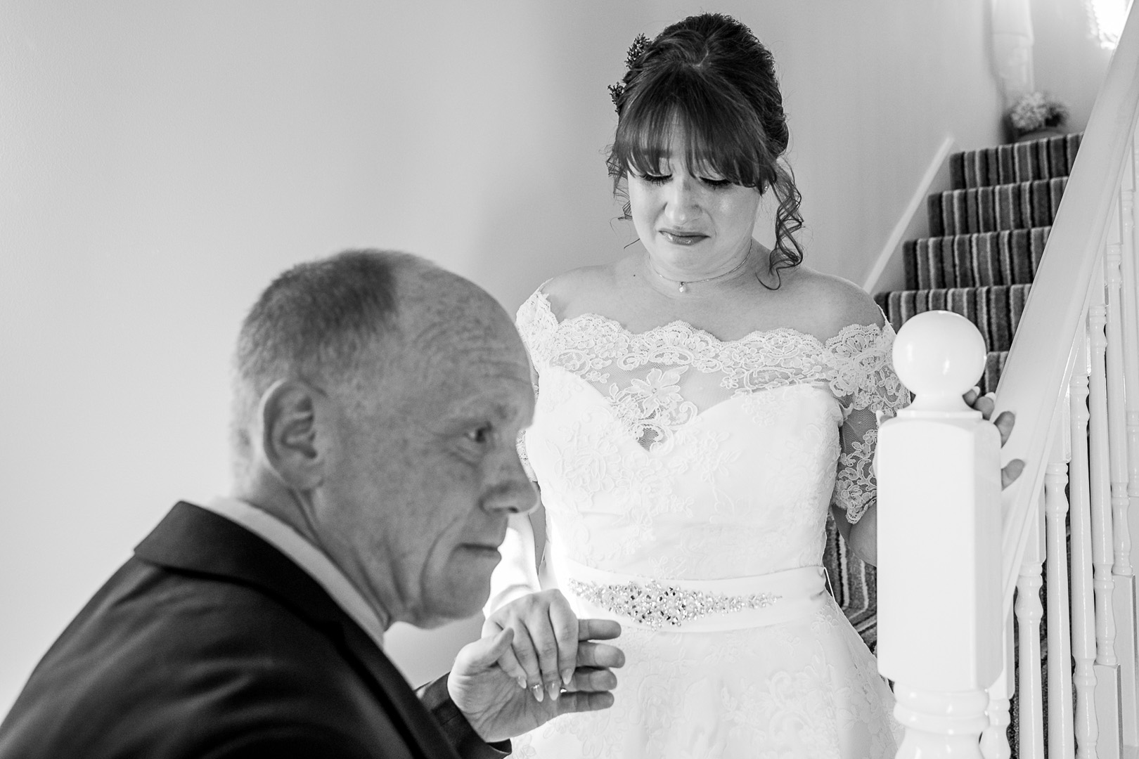 Emotional bride and father seeing her in her dress on her wedding day