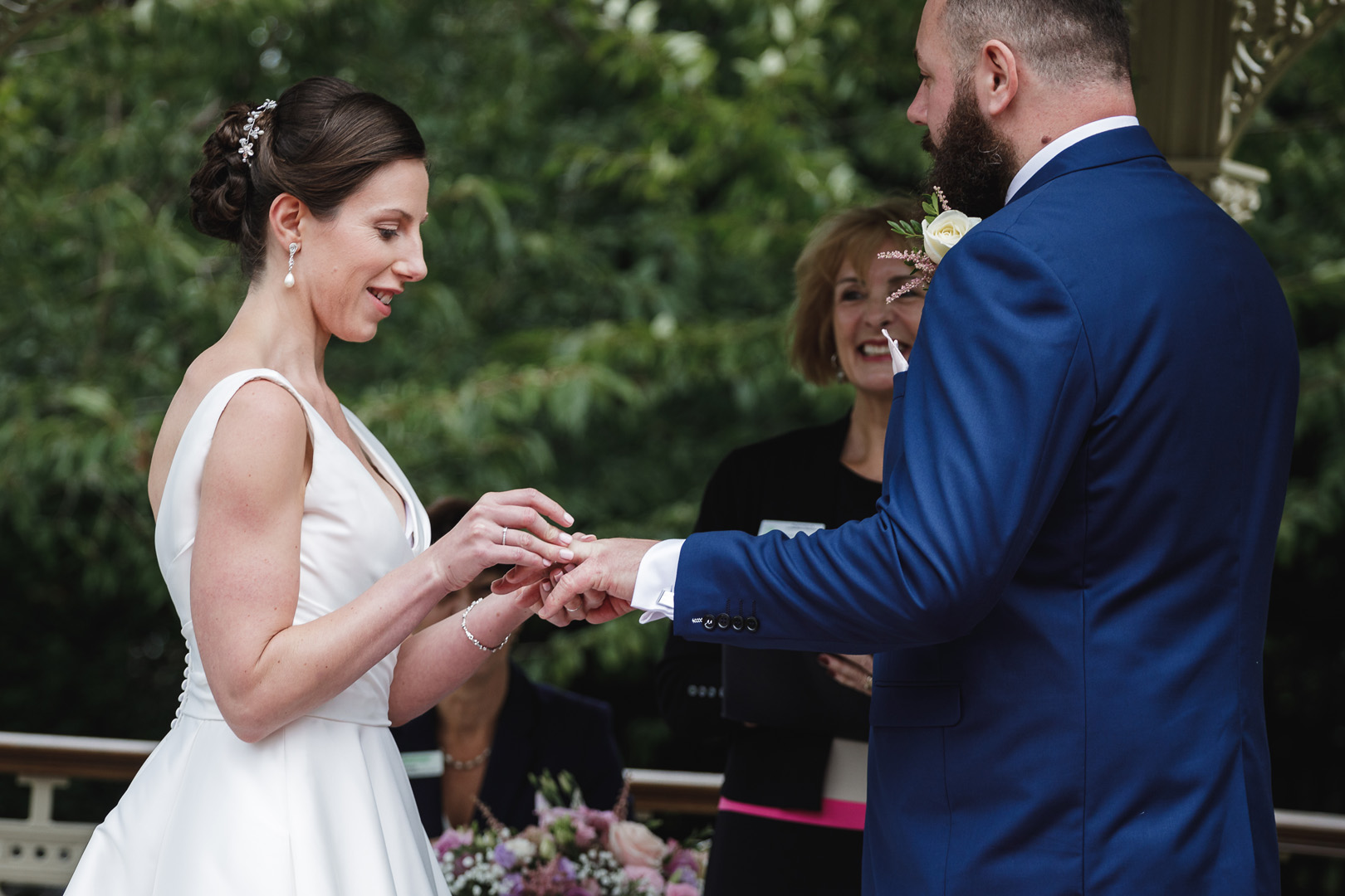 Bride slipping wedding ring on to groom's hand at this west retford hotel wedding