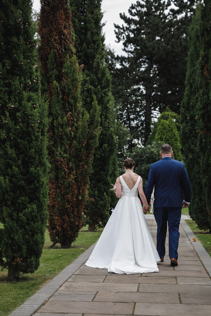 bride and groom on the tree lined path at their west retford hotel wedding