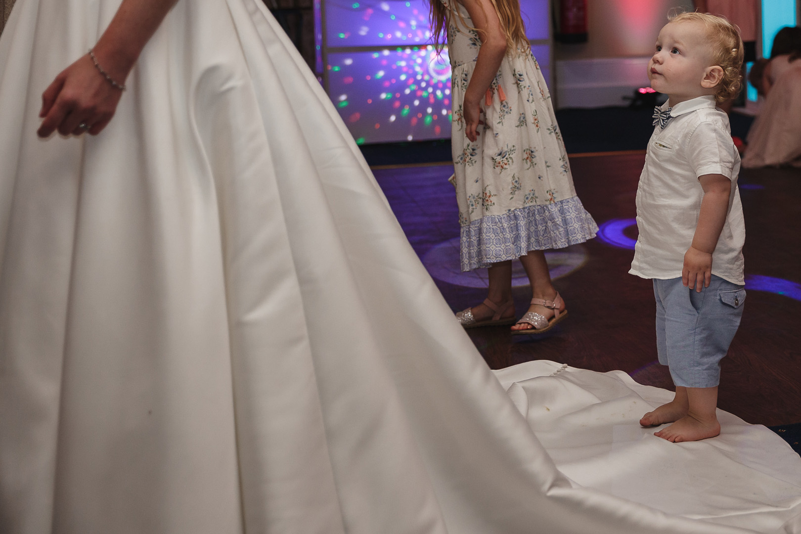 little boy standing on brides wedding dress